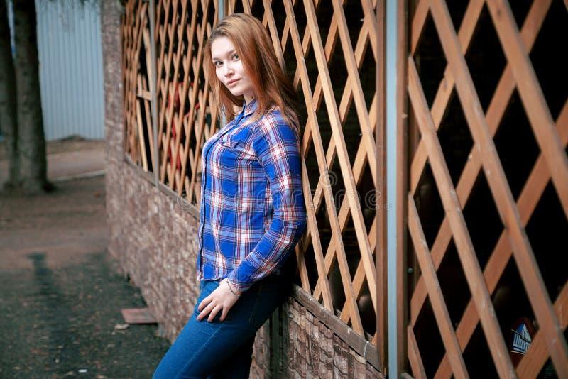 Porträt eines schönen Mädchens Lächeln, werfend auf Kamera auf in einem blauen Hemd in einem Käfig Auf dem hölzernen Gittergitter lizenzfreie stockfotografie