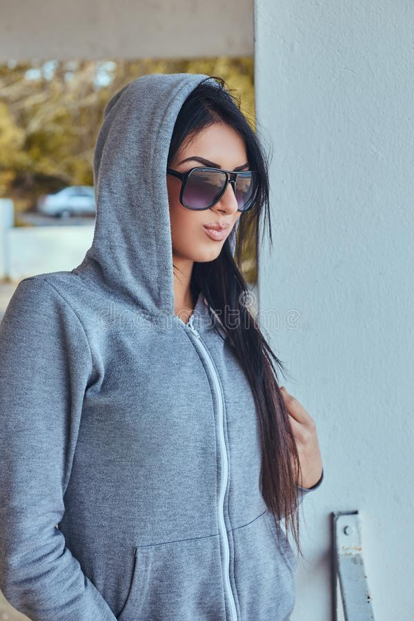 Porträt eines schönen Mädchens mit der gebräunten Haut, die einen grauen Hoodie und Sonnenbrille, lächelnd trägt und hält Hände i stockfotos