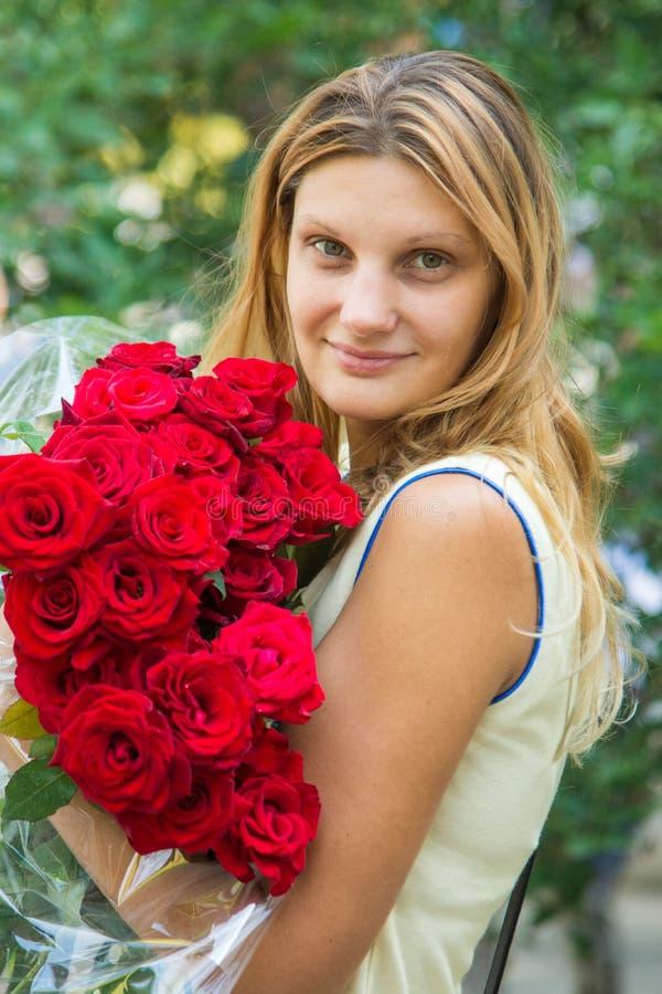 Porträt eines schönen Mädchens mit einem Blumenstrauß von Rosen in ihren Händen lizenzfreies stockbild