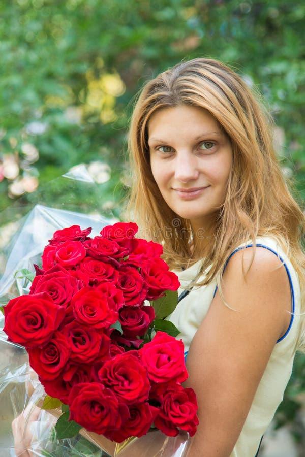 Porträt eines schönen Mädchens mit einem Blumenstrauß von Rosen in ihren Händen lizenzfreie stockfotografie