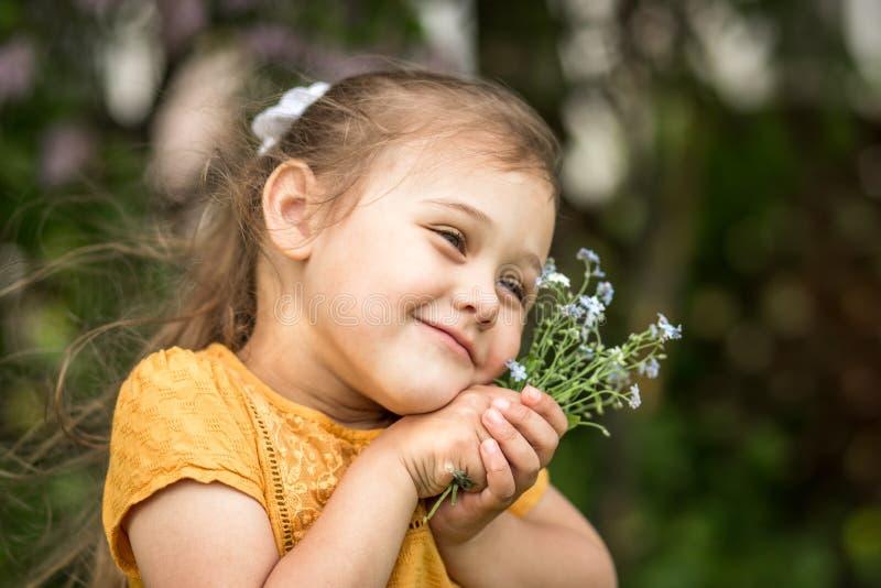 Porträt eines schönen Mädchens mit einem Blumenstrauß von Vergissmeinnichten stockfoto