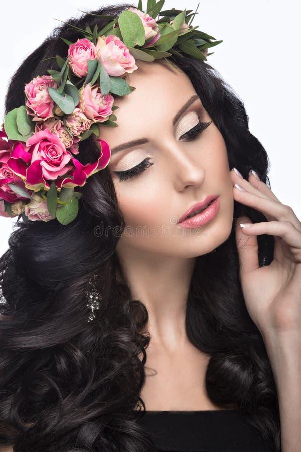 Porträt eines schönen Mädchens mit einem leichten Make-up und vielen Blumen in ihrem Haar Eine Wiese mit blühenden Apfelbäumen Sc lizenzfreie stockfotos