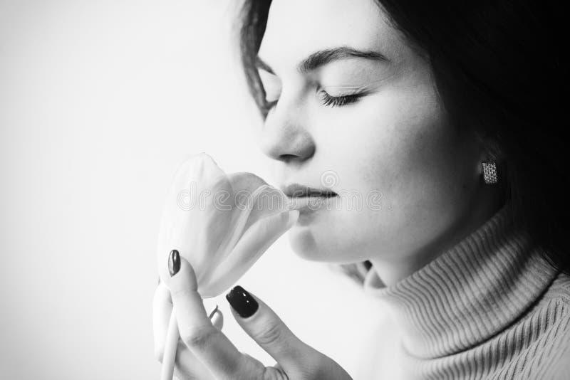 Porträt eines schönen Mädchens mit einer Tulpe stockfotografie