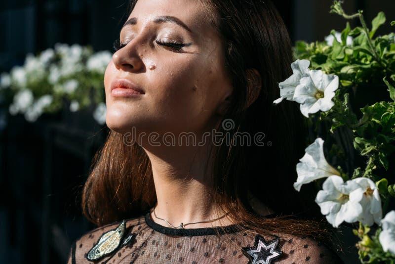 Porträt eines schönen Mädchens, Nahaufnahmegesicht nahe weißen Blumen, Brunettemädchen, schloss ihre Augen Schwarze Kleidung stockfoto