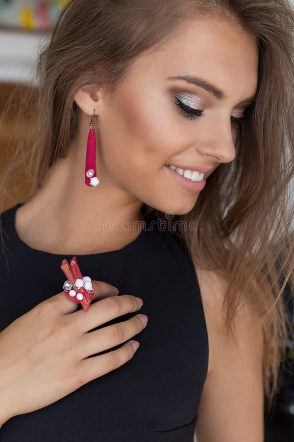 Porträt eines schönen netten leichten schönen jungen Mädchens mit schneeweißem Lächeln mit hellem Make-up im schwarzen Abendkleid lizenzfreies stockbild