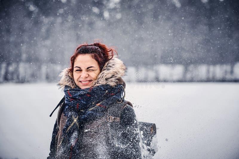 Porträt eines schönen Rothaarigemädchens, das warme Kleidung mit dem Rucksack steht nahe einem Winterwald trägt stockfoto