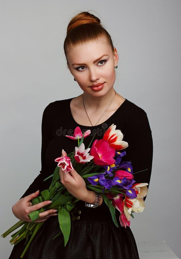 Porträt eines schönen rothaarigen Mädchens, das einen großen Blumenstrauß hält lizenzfreie stockbilder