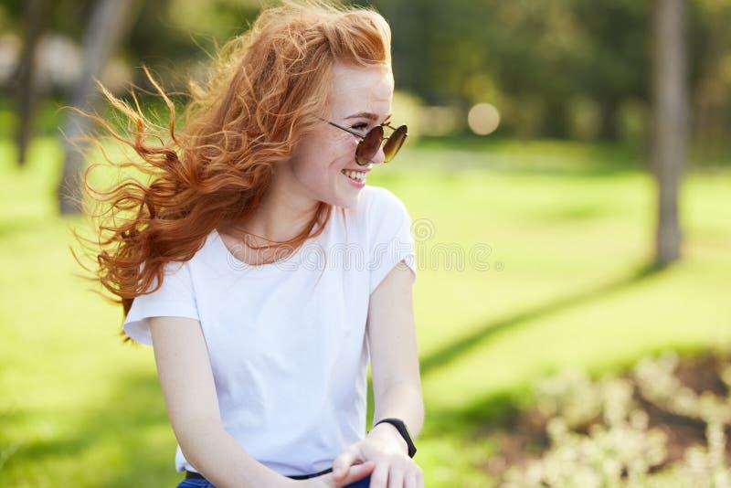Porträt eines schönen rothaarigen Mädchens, das im Park sitzt und weg schaut Der Wind entwickelt ihr Haar und das Mädchenlächeln stockfotos