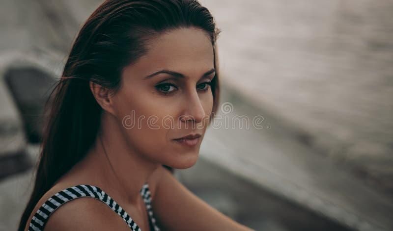 Porträt eines schönen traurigen Brunette durch den Fluss stockbild