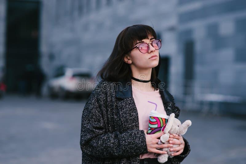 Porträt eines schönen und stilvollen Mädchens in den Gläsern, die einen Kaffee und ein weiches Spielzeug auf dem Hintergrund der  stockbilder