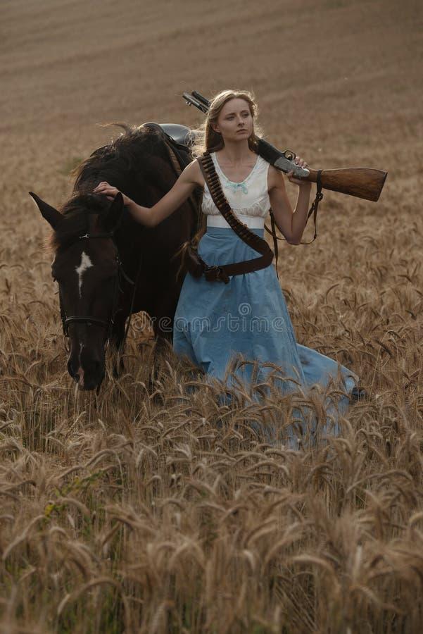 Porträt eines schönen weiblichen Cowgirls mit Schrotflinte vom wilden Westreiten ein Pferd im Hinterland stockfotografie