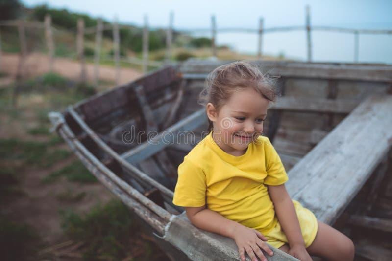 Porträt eines schüchternen Mädchens, das in einem alten Boot an einem Sommerabend sitzt lizenzfreie stockbilder