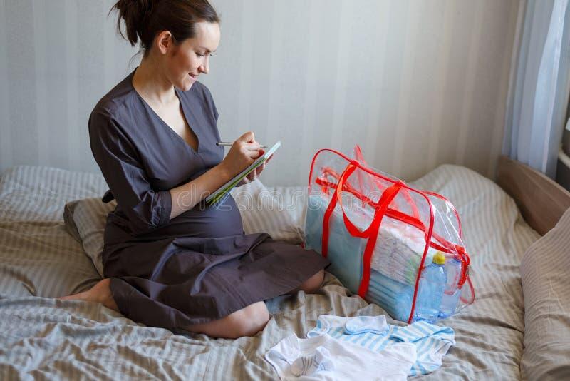 Porträt eines schwangeren Mädchens auf dem Bett sammelt Sachen im Krankenhaus auf der Liste stockbild