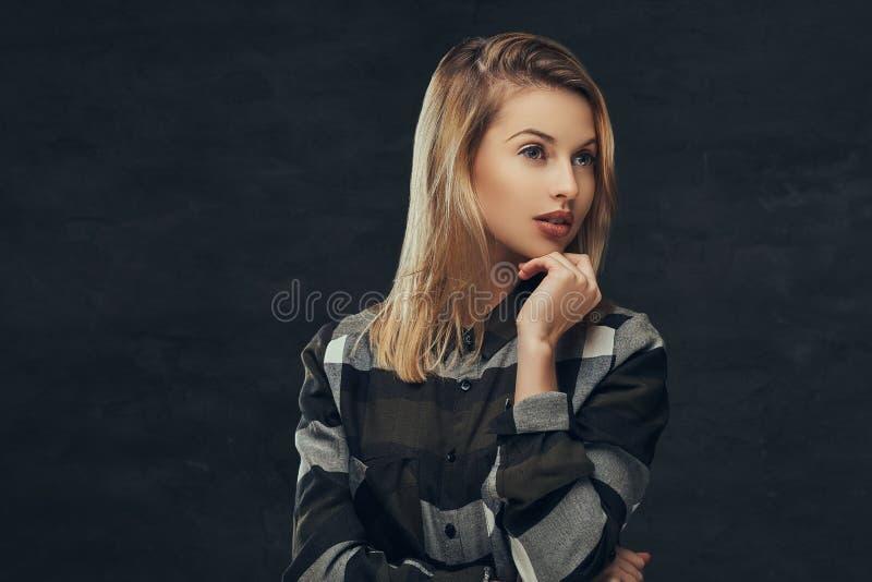 Porträt eines sexy blonden Mädchens in einem Vlieshemd, werfend in einem Studio auf lizenzfreies stockbild