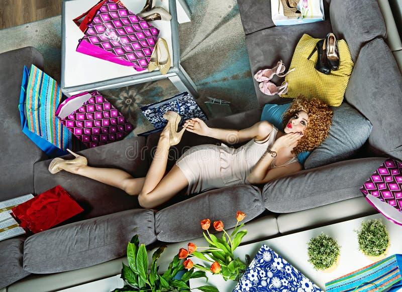 Porträt eines shopaholic Lügens unter vielen Einkaufstaschen stockfotografie