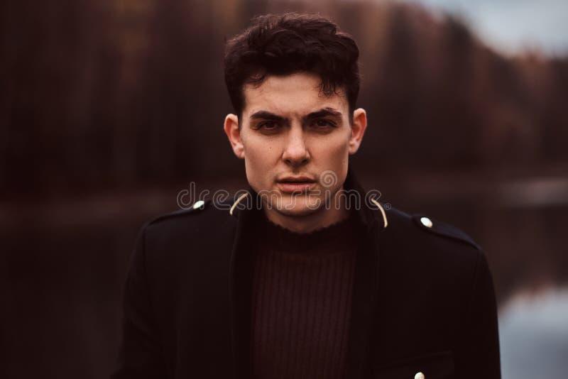Porträt eines sinnlichen jungen Mannes, der einen schwarzen Mantel im Herbstwald trägt stockfotografie