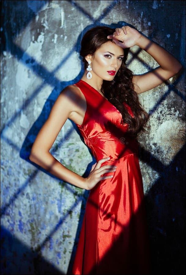 Porträt eines sinnlichen sexy schönen gelockten Mädchens in einem roten Kleid a stockfotografie