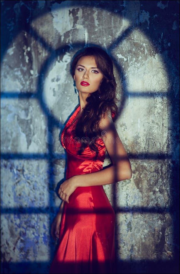 Porträt eines sinnlichen sexy schönen gelockten Mädchens in einem roten Kleid a stockbilder