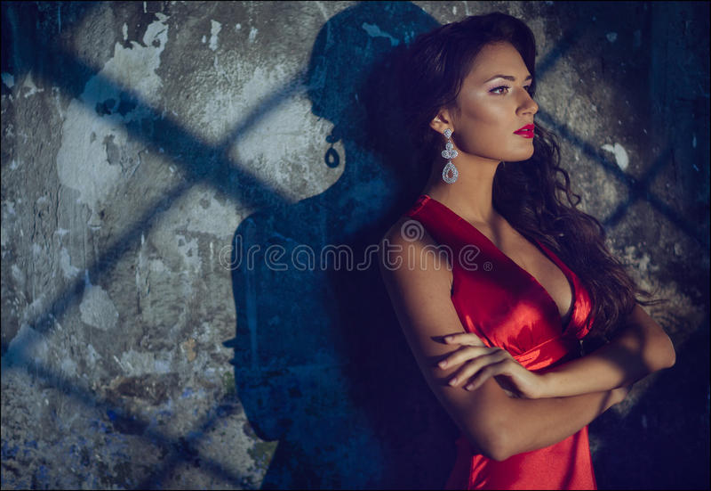 Porträt eines sinnlichen sexy schönen gelockten Mädchens in einem roten Kleid a stockfotos