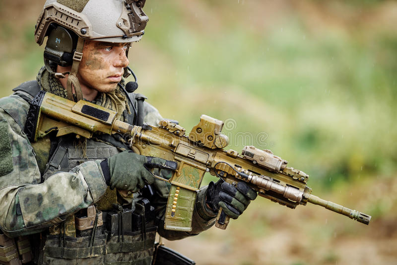 Porträt eines Soldaten im Schlachtfeld mit einem Gewehr stockfotografie