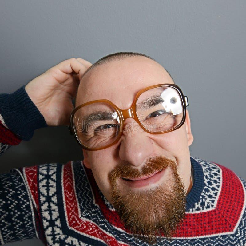 Porträt eines Sonderlings mit Gläsern und Retro- Strickjacke gegen grauen Hintergrund stockbilder