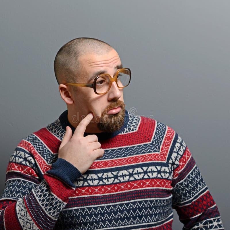 Porträt eines Sonderlings mit Gläsern und Retro- Strickjacke gegen grauen Hintergrund stockfotografie