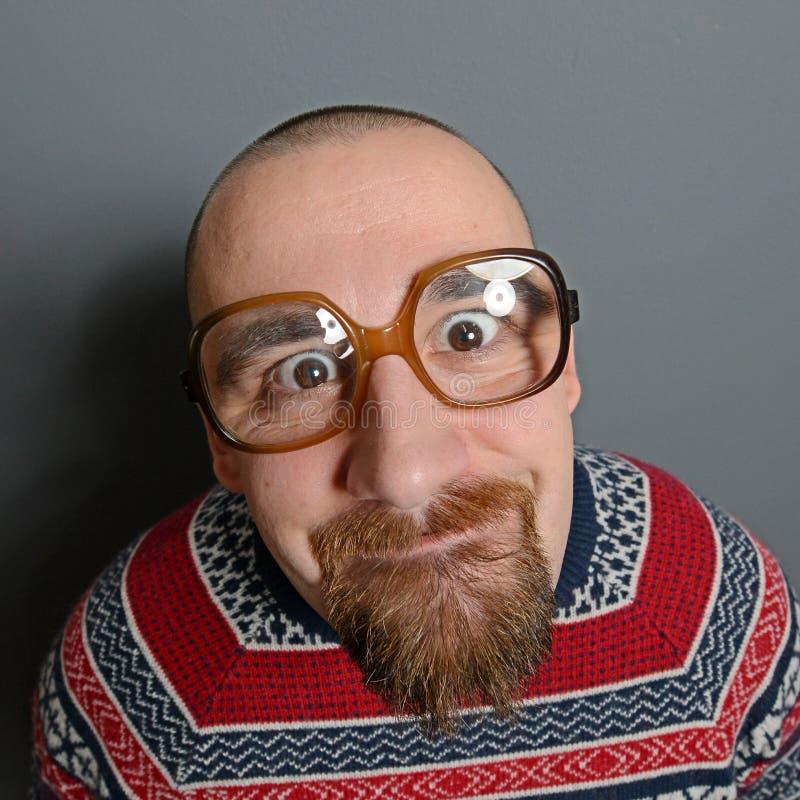 Porträt eines Sonderlings mit Gläsern und Retro- Strickjacke gegen grauen Hintergrund stockfotos