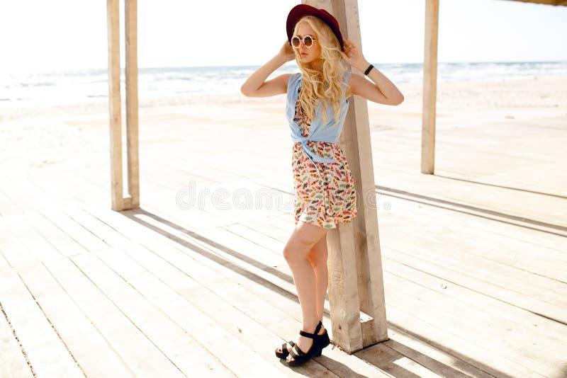 Porträt eines stilvollen blonden Mädchens mit runder Sonnenbrille, Wellenhaar und Burgunder-Hut, genießen das Sonnenlicht in Meer lizenzfreies stockbild