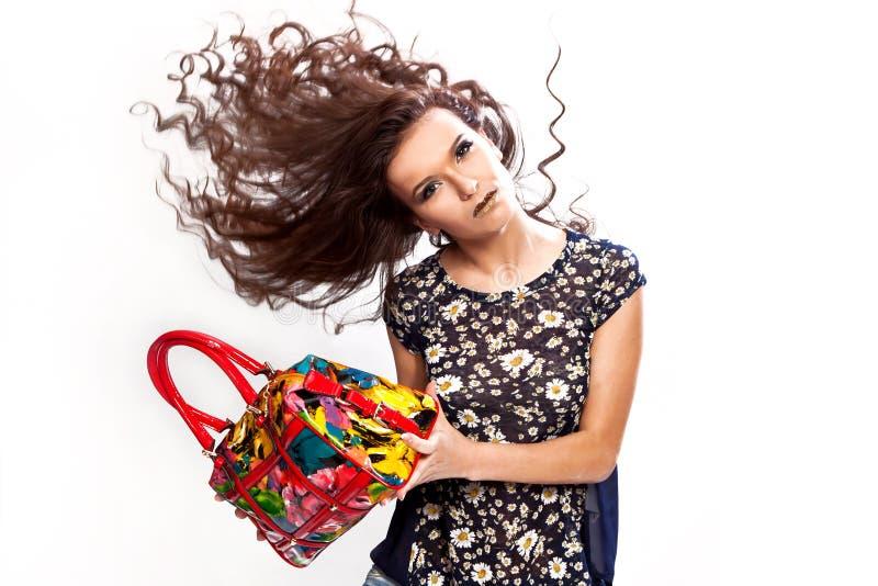 Porträt eines stilvollen Mädchens mit einer Lackledertasche in ihren Händen stockfotografie