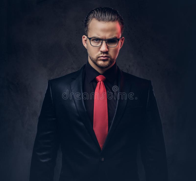Porträt eines stilvollen Mannes in einem schwarzen Anzug und in einer roten Bindung Lokalisiert auf einem dunklen Hintergrund stockfotos