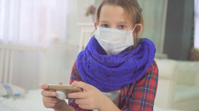 Porträt eines Teenagers mit ärztlicher Maske, der die Kamera im Bett zu Hause ansieht stockbilder