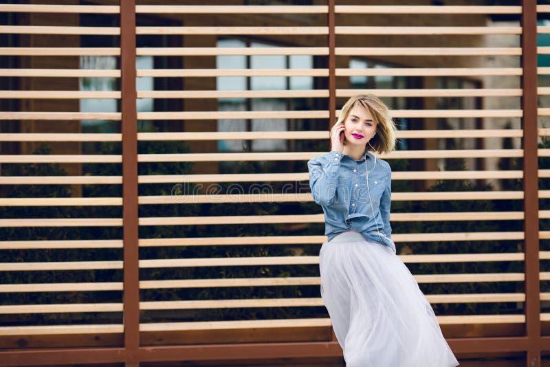 Porträt eines träumerischen Mädchens mit dem kurzen blonden Haar des Fliegens und den hellen rosa Lippen hörend Musik auf einem S lizenzfreie stockbilder