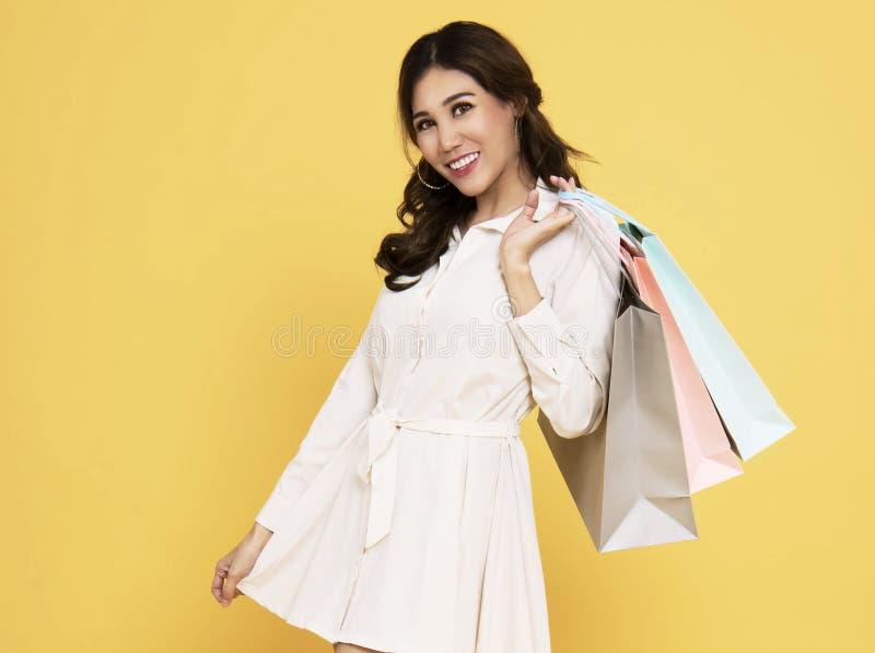 Porträt eines tragenden Kleides des aufgeregten schönen asiatischen Mädchens, das Einkaufstaschen lokalisiert auf gelbem Hintergr stockfoto