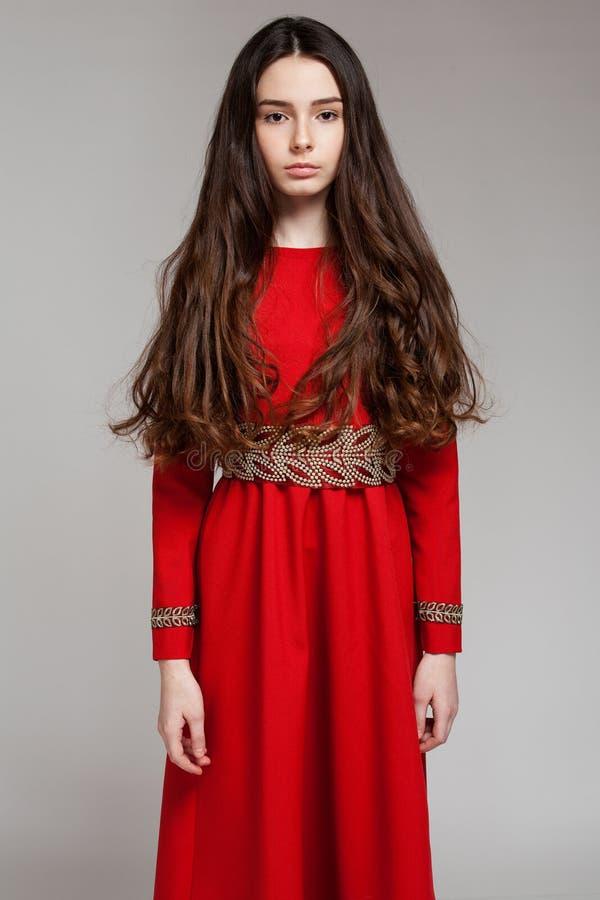 Porträt eines traurigen Brunettemädchens mit dem langen Haar in einem roten Kleid lizenzfreie stockbilder