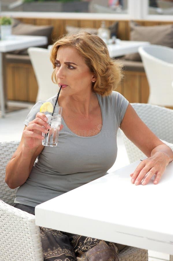 Porträt eines Trinkwassers der Frau vom Glas am Restaurant lizenzfreie stockfotos