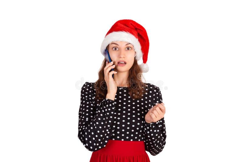 Porträt eines verwirrten netten Mädchens im Kleidergespräch am Handy emotionales Mädchen im Weihnachtsmann-Weihnachtshut lokalisi lizenzfreies stockbild