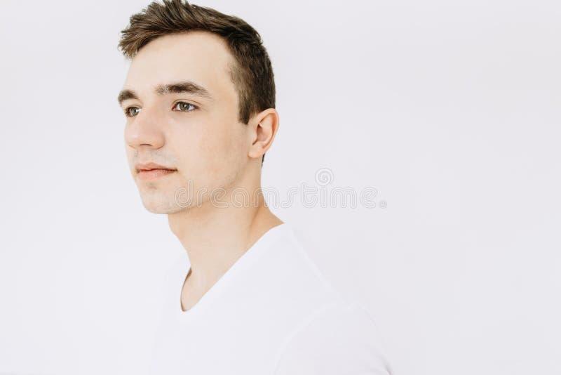 Porträt eines weißen jungen Kerls in einem weißen T-Shirt, lokalisiert auf einem weißen Hintergrund lizenzfreie stockfotografie