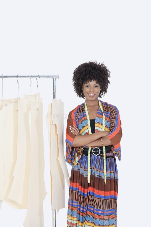 Porträt eines weiblichen Designers des Afroamerikaners mit nähenden Mustern auf Kleiderständer über grauem Hintergrund stockfotos