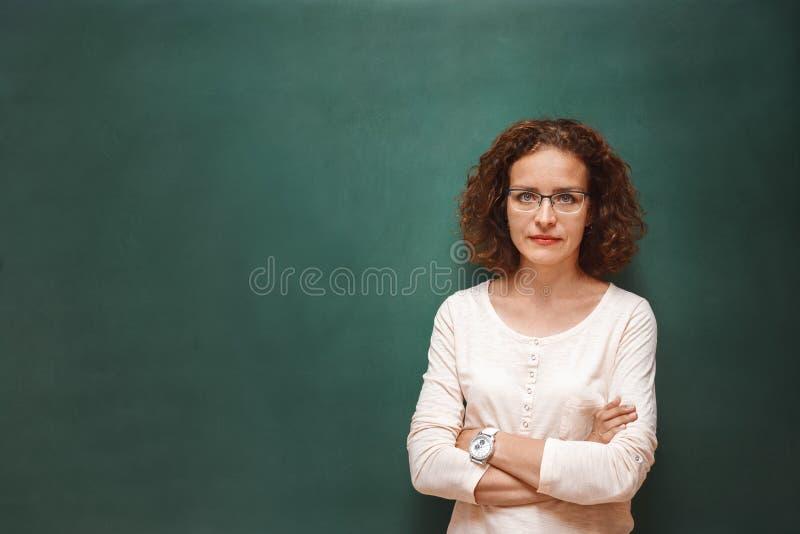 Porträt eines weiblichen Lehrers nahe der Schultafel lizenzfreies stockbild
