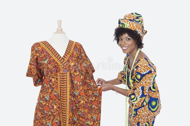 Porträt eines weiblichen Modedesigners des Afroamerikaners, der an dashiki über grauem Hintergrund arbeitet stockfotografie