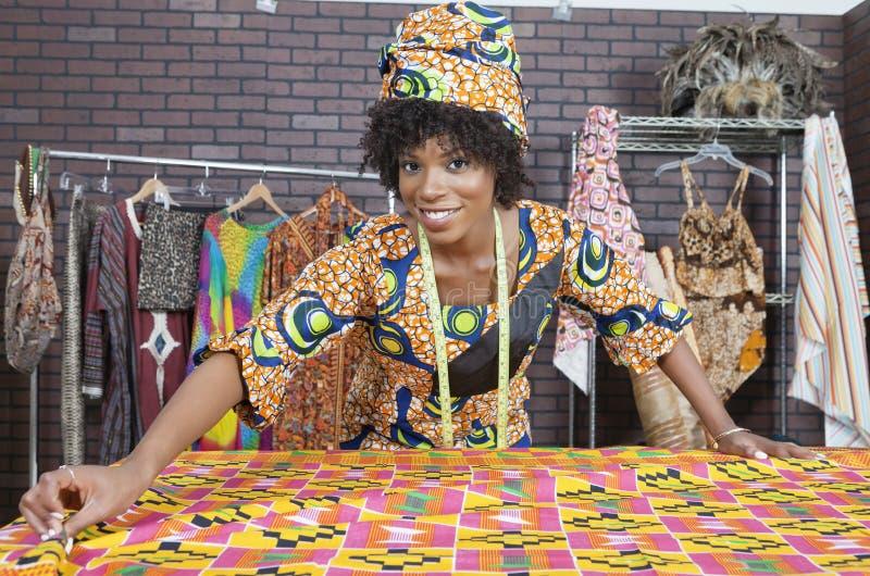 Porträt eines weiblichen Modedesigners des Afroamerikaners, der an einem Musterstoff arbeitet lizenzfreie stockfotos