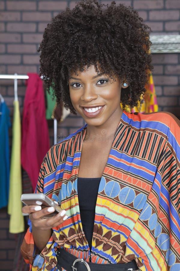 Porträt eines weiblichen Modedesigners des Afroamerikaners, der Handy verwendet lizenzfreies stockbild