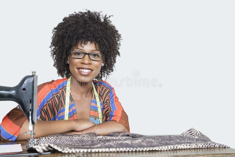 Porträt eines weiblichen Modedesigners des Afroamerikaners mit Nähmaschine und Stoff über grauem Hintergrund stockfoto