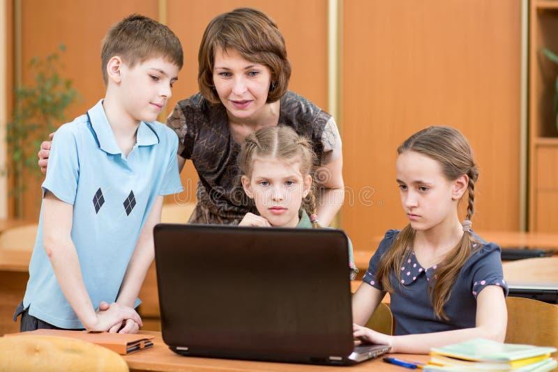 Porträt einiger Kinder und ihres Lehrers, die Laptopschirm im Klassenzimmer betrachten lizenzfreies stockbild