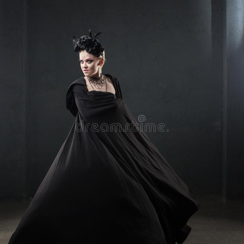 Porträt eleganten gotischen Blondine Mädchen im Kranz von schwarzen Blumen und von schwarzem Mantel lizenzfreie stockfotos