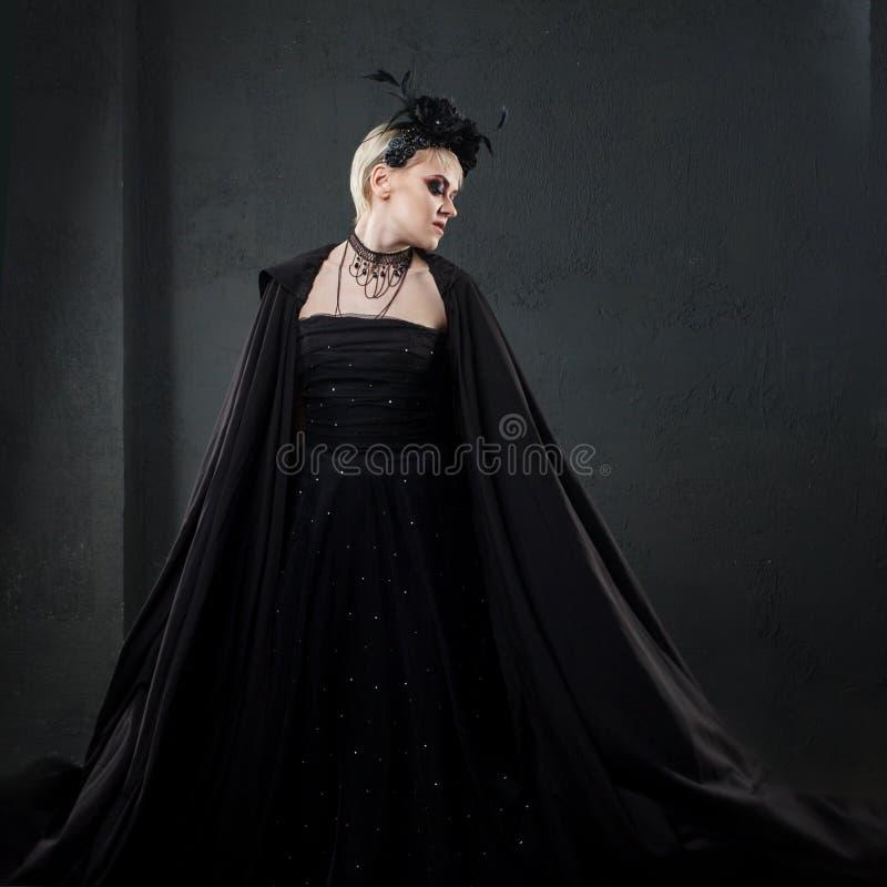 Porträt eleganten gotischen Blondine Mädchen im Kranz von schwarzen Blumen und von schwarzem Mantel stockbilder
