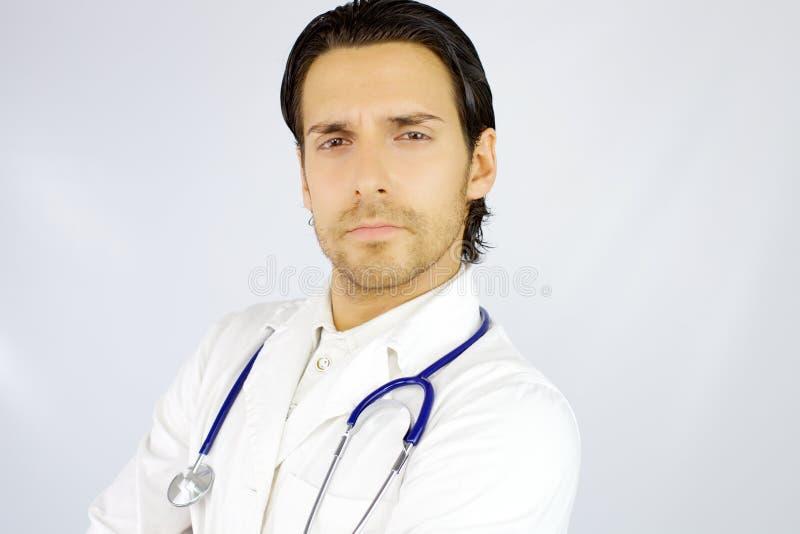 Porträt ernsten hübschen amerikanischen Doktors, der Kamera schaut stockbilder
