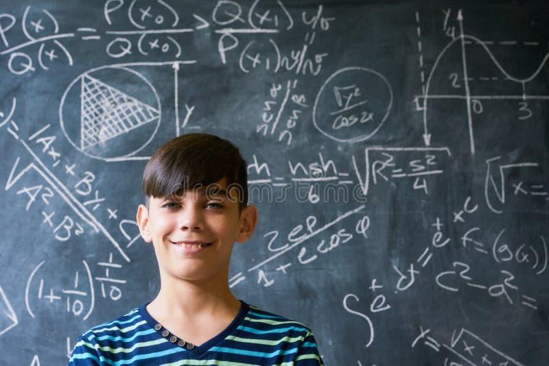 Porträt-Genie-Junge, der an der Kamera während der Mathe-Lektion lächelt lizenzfreies stockfoto
