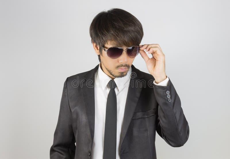 Porträt-Geschäftsmann im schwarzen Anzug, der Brillen auf mittlerer Frequenz berührt lizenzfreie stockfotos