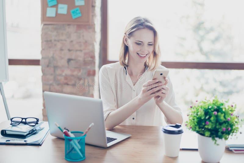 Porträt glücklichen lächelnden frohen Sekretärs das Schreibensms auf ihrem s lizenzfreie stockfotos